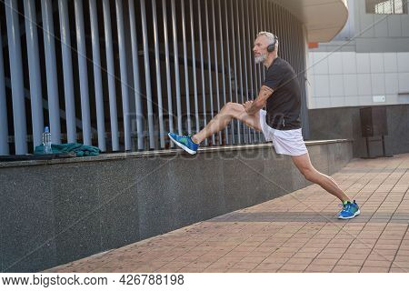 Full Length Shot Of Sportive Middle Aged Man In Sportswear And Headphones Looking Away, Warming Up H