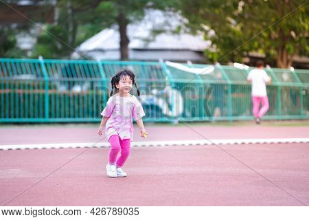 Cute Asian Girl Jogging At The Stadium. Children Wear Pink T-shirts And Leggings, White Sneakers. Ch