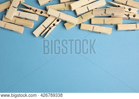 Many Wooden Clothespins On Light Blue Background, Flat Lay. Space For Text