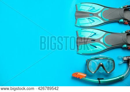 Pair Of Turquoise Flippers And Mask On Light Blue Background , Flat Lay. Space For Text