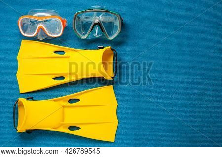 Pair Of Yellow Flippers And Masks On Blue Fabric, Flat Lay. Space For Text