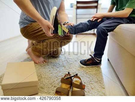Online Shopping For Baby And Kids. Father Helping Fitting Shoes For His Child At Home. Free Of Charg