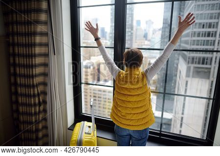 Traveler With Suitcase Looks And Admires Of Amazing View The Skyscrapers Of Manhattan Outside Window