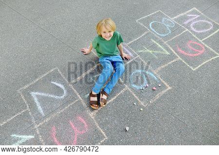 Little Boy Sitting On Hopscotch Drawn On Asphalt. Child Playing Hopscotch Game On Playground On Spri