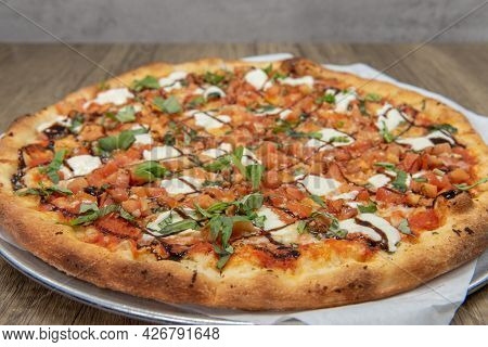 Crispy Crust On This Bruschetta Pizza Loaded With Toppings And Drizzled With Sauce For Presentation.