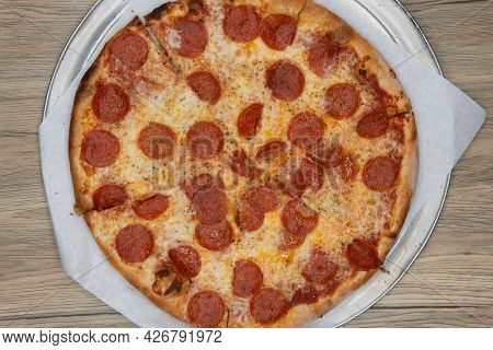 Overhead View Of Pepperoni Pizza With Crispy Crust And Melted Cheese For A Perfect Lunch Date.