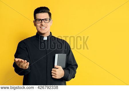 Priest In Cassock With Bible On Yellow Background. Space For Text