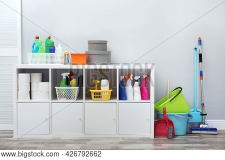 Shelving Unit With Detergents And Cleaning Tools Near Light Grey Wall Indoors