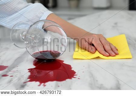 Woman Cleaning Spilled Wine On White Marble Table Indoors, Closeup