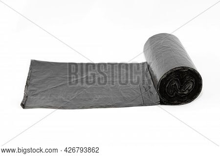 Black Polyethylene Garbage Bags On White Background - Close-up. The Roll Of Plastic Junk Package