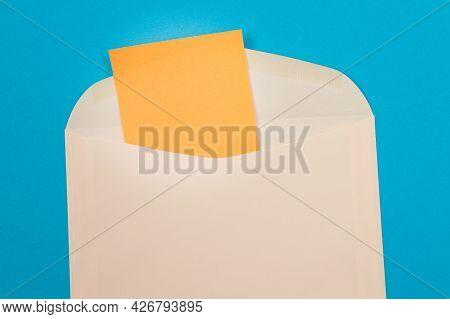 Beige Envelope With Blank Orange Sheet Of Paper Inside, Lying On Blue Background - Mock Up With Copy