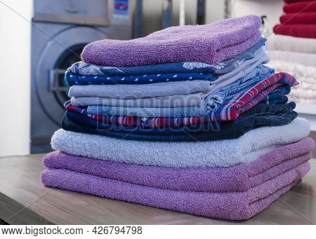 Stack Of Folded Pastel Colors Clothes In A Laundry. Clean And Soft Clothes Pile.  Washed And Ironed