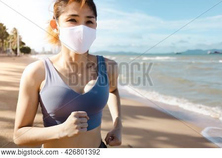 Asian Woman Jogging By The Beach In The Morning Of Warm Summer.