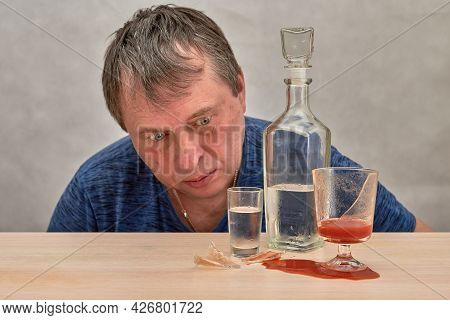 A Drunk Man Looks At Alcohol And A Broken Glass Of Tomato Juice