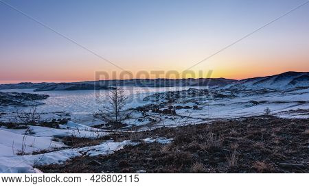 Winter Sunrise In Siberia. The Sky Above The Mountains Is Pink And Orange. Glare Of The Sun On The I