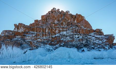 A Red-brown Rock, Devoid Of Vegetation, Against A Blue Sky. Bizarre Shapes, Cracks On The Rocks. The