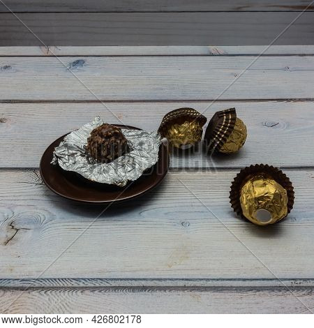 Chocolates Wrapped In Golden Foil Are Scattered On A Wooden Table. One Candy Is Unfolded, Lying On A