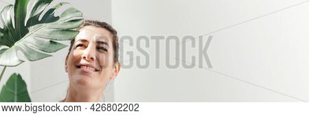 Cheerful woman with a split leaf philodendron
