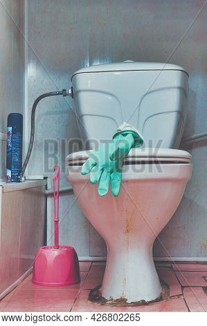 Rubber Glove On The Lid Of An Old Dirty Toilet Bowl