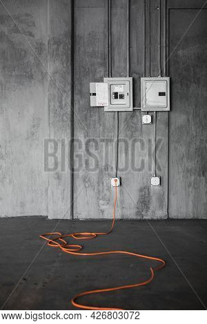 Orange electric wire plug to wall socket