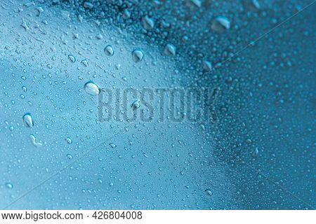 Abstract Background With Raindrops And Beautiful Blue Bokeh. The Concept Of Autumn And The Cold Stor