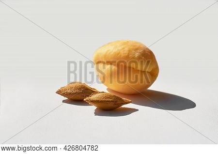 Apricot And Two Apricot Seeds On A Gray Textured Background.