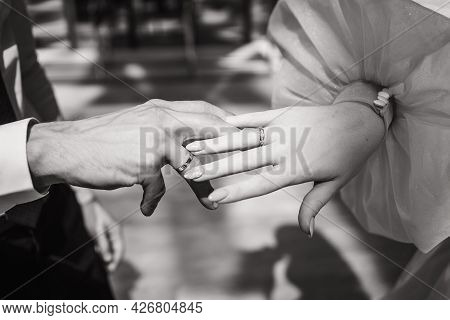 Close-up Of The Brides And Grooms Hands. Black And White Photo Of The Bride And Groom. A Place For T