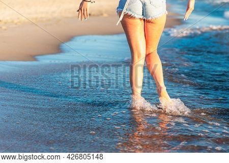 Woman Legs And Feet Walking On The Sand Of The Beach With The Sea Water In The Background.walking On