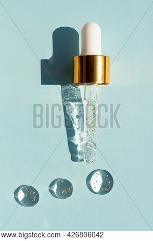 Liquid Serum And Dropper On A Blue Background Top View. 24k Gold Serum Drops In The Form Of A Circle