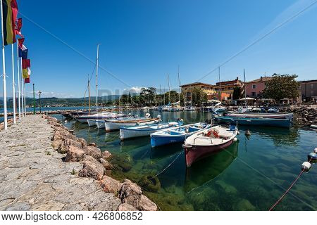 Port Of The Small Village Of Cisano With Small Boats Moored, Tourist Resort On The Coast Of Lake Gar