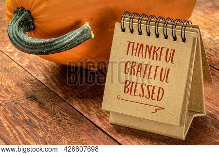 thankful, grateful, blessed inspirational words - a pumpkin with a handwriting in a spiral sketchbook, Thanksgiving holiday concept