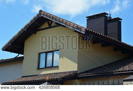 An Outside View Of An Attic With Stucco Walls, Clay, Ceramic Roof, Two Chimneys, Roof Gutters And An