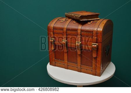 Rich Decorated Leather Bound Chest With Four Straps Captured On Rounded White Table In Front Of Gree