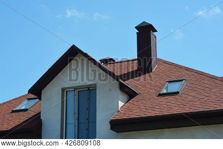 A Close-up Of An Asphalt Shingled Roofing Construction With Attic Skylights, A Chimney, Soffit, Fasc
