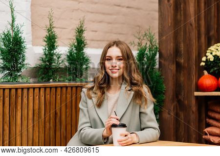 Very Beautiful Young Woman, Sit In Cafe And Drink Coffee Or Tea With Croissant, Street Front View
