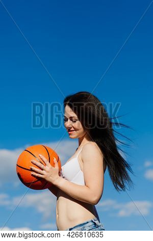 Young Athletic Female, In Top And Sweatpants, Playing With Ball On Basketball Court Outdoors.