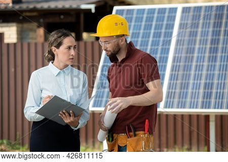 Serious female engineer explaining contractor where to install solar panels in backyard