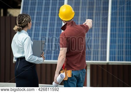 Contractor showing businesswoman solar panel facility he installed and explaining details of its maintenance