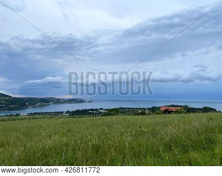 Storm Clouds Running Across The Sky Against The Background Of The Sea And Green Hills On Coast. Scen