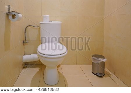 Public Toilet In The Airport Or Restaurant, Cafe. Closeup Of Toilet Bowl And Roll On Toilet Paper Ho