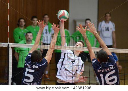 KAPOSVAR, HUNGARY - FEBRUARY 14: Bence Bozoki (C) in action at a Hungarian Championship volleyball game Kaposvar (w) vs. PTE-PEAC (b), February 14, 2013 in Kaposvar, Hungary