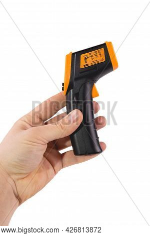 A Man Holds A Yellow-black Pyrometer. A Device For Non-contact Temperature Measurement. Studio Photo