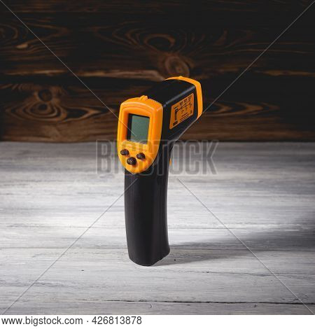 Yellow-black Pyrometer On A Wooden Background. A Device For Non-contact Temperature Measurement. Stu