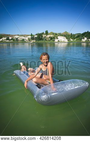 Two Little Cute Girls In Swimsuits Swim On An Inflatable Mattress On A Blue Career Lake.