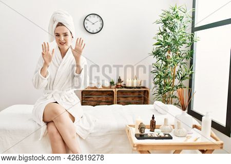 Young blonde woman wearing bathrobe at wellbeing spa showing and pointing up with fingers number nine while smiling confident and happy.