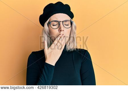 Young blonde girl wearing french look with beret bored yawning tired covering mouth with hand. restless and sleepiness.