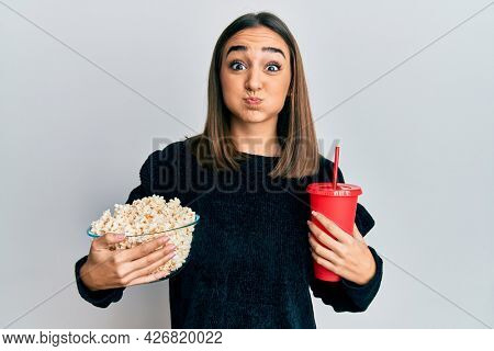 Young brunette girl eating popcorn and drinking soda puffing cheeks with funny face. mouth inflated with air, catching air.