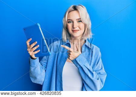 Young blonde girl using touchpad device smiling happy pointing with hand and finger