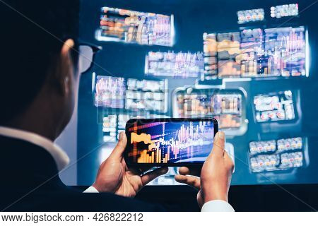 Business Man Using Mobile Phone App Analytics For Financial Stock Market Graph Trading