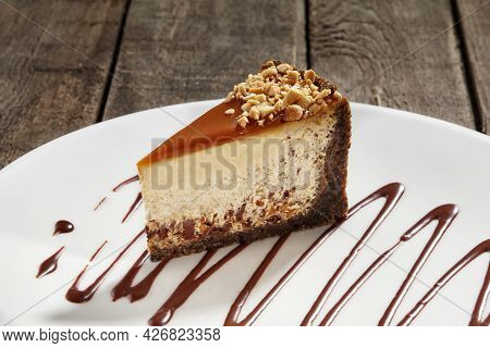 Slice Of Cheesecake With Chocolate, Nuts And Caramel On Shortcrust Pastry